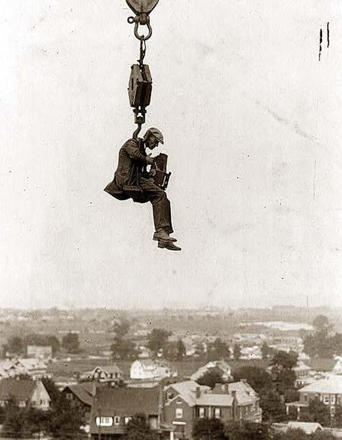 Photographer with camera suspended from hook
