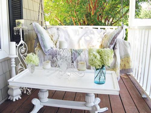 White porch swing with porch table and candles and flowers