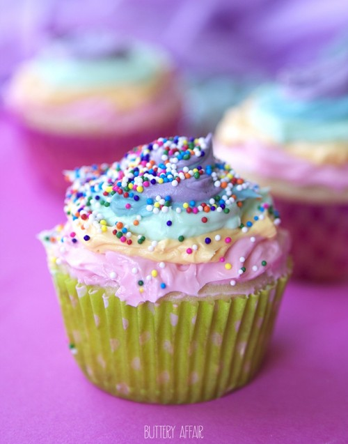 Vanilla-cupcakes-with-rainbow-frosting-and-strawberry-filling-804x1024_large