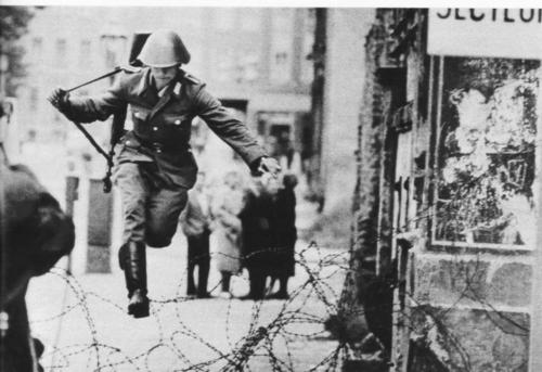 East German soldier leaping barbed wire of the Berlin Wall, to freedom.
