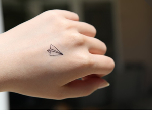hand, paper plane, and tattoo image