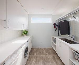 laundry room., custom storage cabinet, and floating modern racks image
