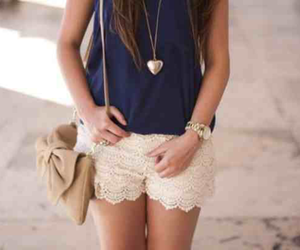 heart necklace, navy top, and tan purse image