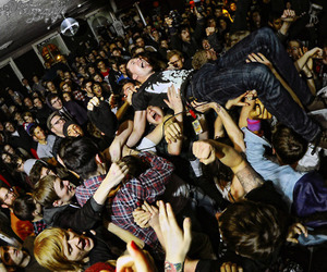 boy and crowd surfing image