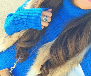 blue ring, beige purse, and brown curled hair image