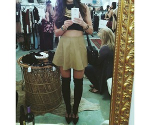 beige skirt, black knee high boots, and black crop top image