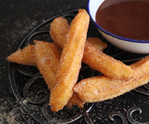 chocolate sauce, churros, and sweets image