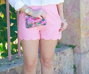 gold watch, black curled hair, and pink shorts image