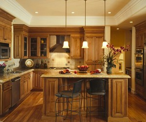 appliances, wooden cabinets, and bar image