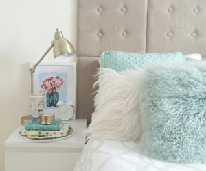 gold lamp, faux fur pillows, and white bed side table image