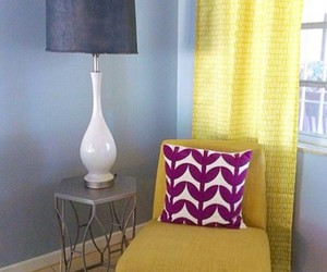 white lamp, yellow chair, and silver tables image