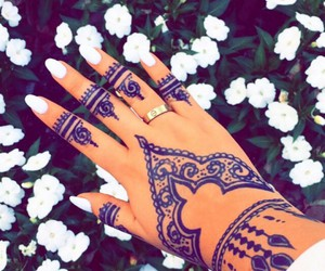 white nails, white flowers, and black henna tattoos image