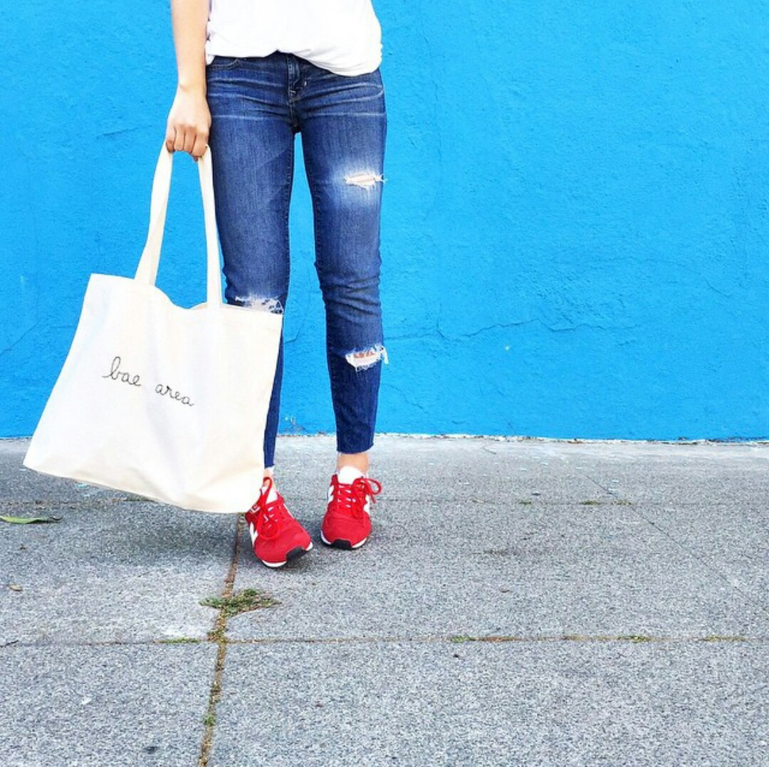 white tote bag, blue ripped jeans, and white t-shirt image