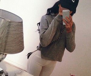 black purse, grey long sleeve, and white high waisted jeans image