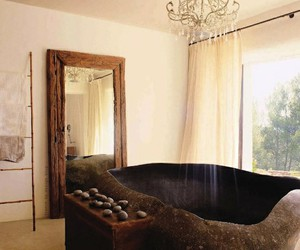 Habitats / bath space made out of a giant pebble shaped granite piece brought back from Bali and sculpted as a bath receiver