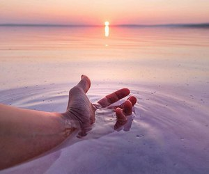 hand, ocean, and suncet image
