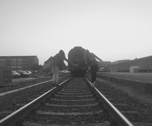 black and white, holding hands, and rails image