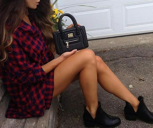 long curled hair, black ankle booties, and black leather purse image