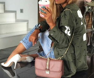 army green jacket, studded purse, and white pumps image