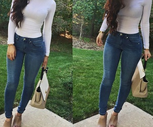 blue jeans, white turtleneck, and wavy brown hair image
