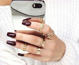 finger tattoo, gold rings, and burgundy nails image