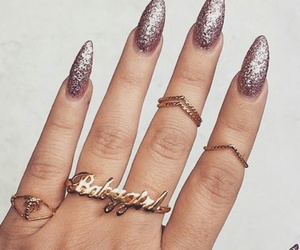 gold rings, glitter almond nails, and pink glitter nails image