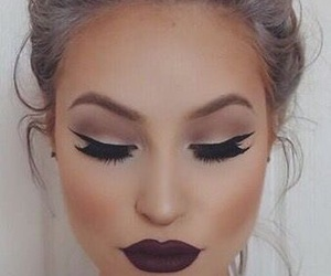 cat eye, messy bun, and dark lip image