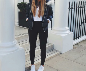 black coat, black skinny jeans, and white sneakers image