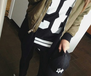 black t-shirt, gold necklaces, and white sneakers image