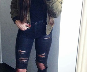 black turtleneck, long wavy brown hair, and black ripped jeans image