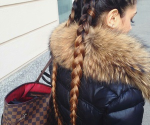 flawless eyelashes, brown oversized purse, and black winter coat image