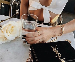 black purse, gold rings, and white roses image