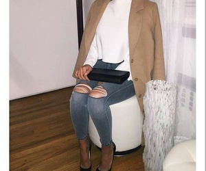 black clutch, blue ripped jeans, and black pumps image