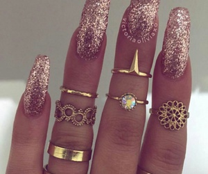 gold mid rings, gold layered rings, and long glitter nails image