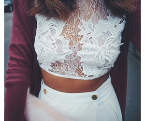 white lace top, fur clutch, and wavy brown hair image