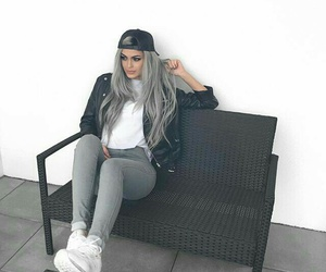 black leather jacket, white sneakers, and black baseball hat image