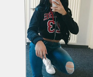 long wavy black hair, black baseball hat, and blue ripped jeans image