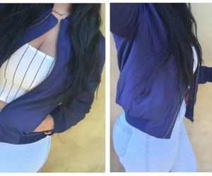gold necklaces, long wavy black hair, and blue high waisted jeans image