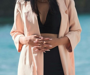layered necklaces, straight black hair, and long pink jacket image