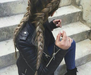 black leather jacket, blue skinny jeans, and long french braids image