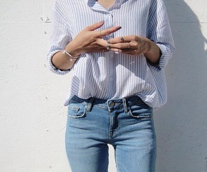 blue shirt, light jeans, and striped shirt image