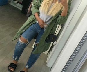 black purse, blue ripped jeans, and long straight blonde hair image