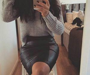 wavy brown hair, grey knit sweater, and black leather skirts image