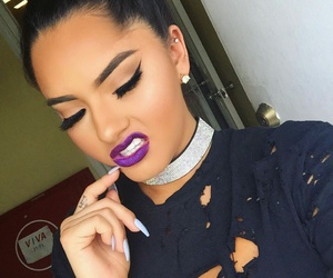 Black Eyeliner, purple lipstick, and rhinestone necklaces image