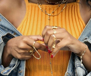 gold chains, red nails, and black curly hair image