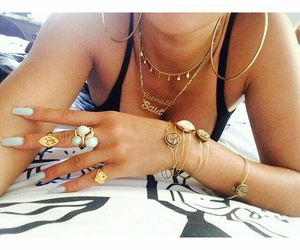 gold chains, gold hoops, and gold bracelets image