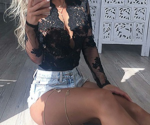 gold necklaces, wavy blonde hair, and black lace bodysuit image