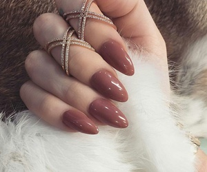 white faux fur rugs, rhinestone rings, and long almond nails image