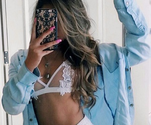 long wavy brown hair, long pink nails, and silver necklaces image