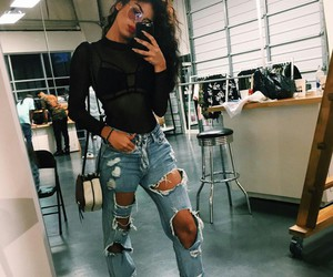 black bra, blue ripped jeans, and black high heels image